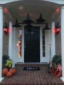 Witches hats with tea lights, pumpkins, ornamental cabbage & flickering porch lights.